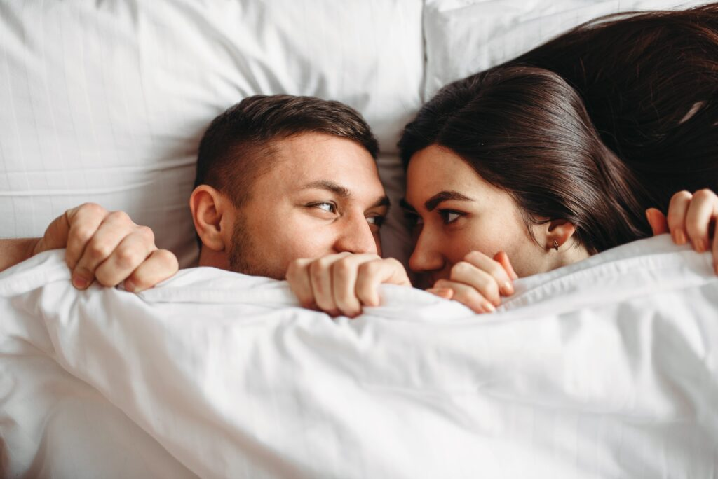 Shy love couple lies on big white bed, top view